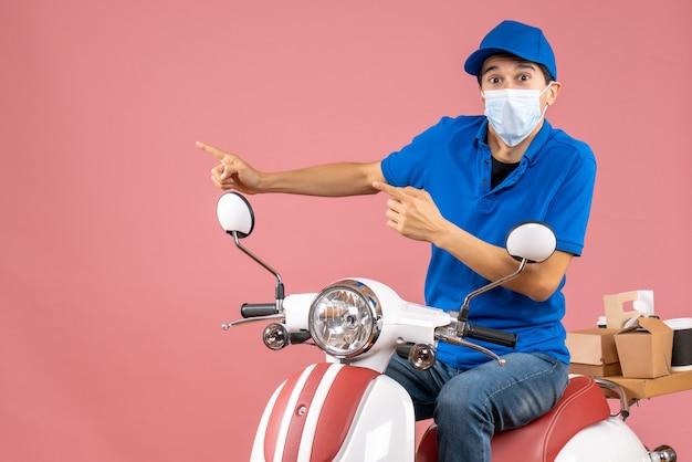 Vista dall'alto del ragazzo delle consegne in maschera medica che indossa un cappello seduto su uno scooter e indica qualcosa sul lato destro su sfondo color pesca pastello