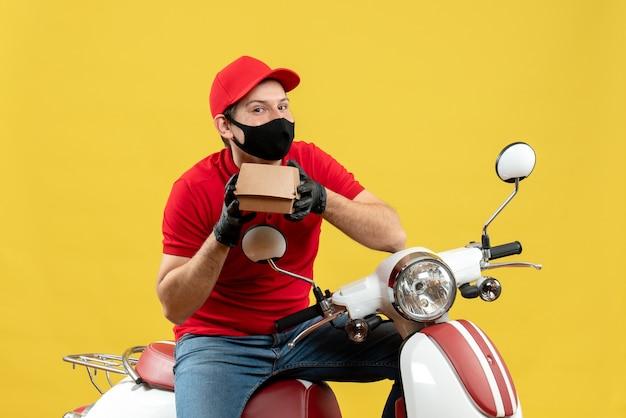 Vista dall'alto del ragazzo delle consegne che indossa guanti di camicetta e cappello rossi nella mascherina medica che si siede sullo scooter che mostra l'ordine
