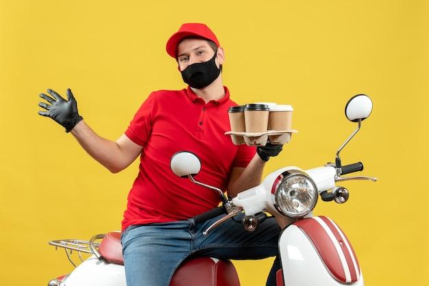Vista dall'alto del ragazzo delle consegne che indossa guanti uniformi e cappello in mascherina medica che si siede sullo scooter che mostra gli ordini che si sentono felici
