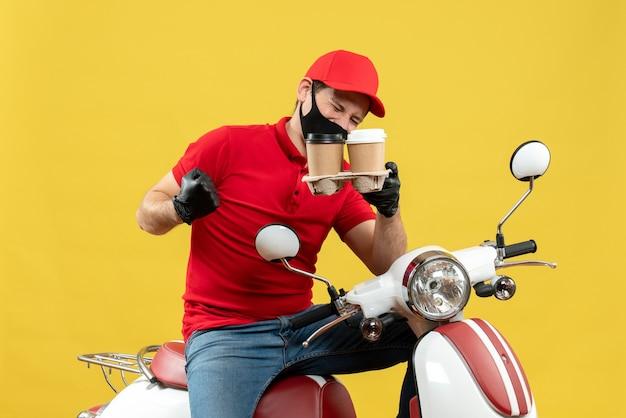 Vista dall'alto del ragazzo delle consegne che indossa guanti uniformi e cappello nella mascherina medica che si siede sullo scooter che mostra gli ordini sentirsi orgogliosi