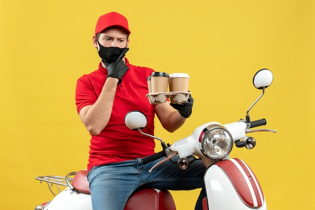 Top view of delivery guy wearing uniform and hat gloves in medical mask sitting on scooter showing orders feeling shocked