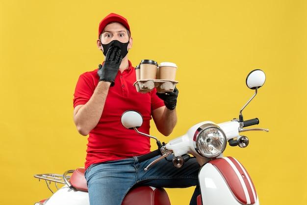 Vista dall'alto del ragazzo delle consegne che indossa guanti uniformi e cappello in maschera medica che si siede sullo scooter che mostra gli ordini che si sentono sorpresi