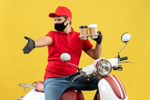 Vista superiore dell'uomo di consegna che indossa guanti uniformi e cappello in mascherina medica che si siede sul motorino che mostra gli ordini che indicano qualcosa