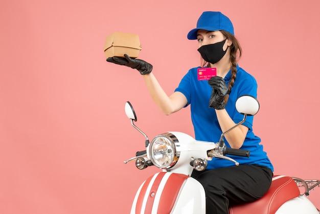 Vista dall'alto del fattorino che indossa maschera medica e guanti seduto su uno scooter con una carta di credito che consegna ordini su sfondo color pesca pastello
