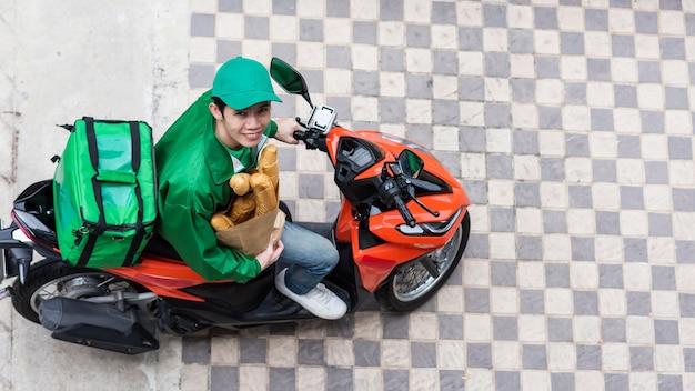 トップ ビューの配達員は、バイクのパン屋さんの紙袋にバゲット パンを保持します。