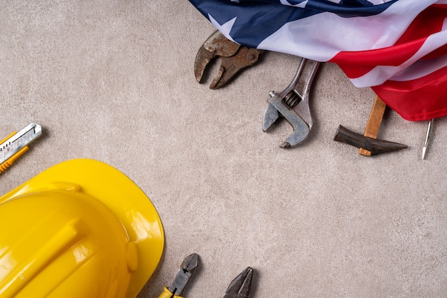 Top view design concept of american labor day with working tools on gray table background.