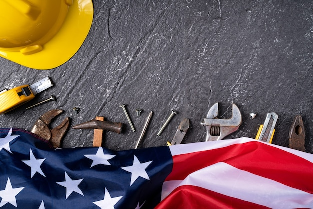 Top view design concept of american labor day with working tools on slate table background.