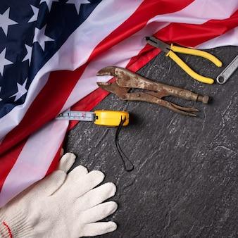 スレートテーブルの背景に作業ツールを使用したアメリカの労働者の日の上面図のデザインコンセプト。