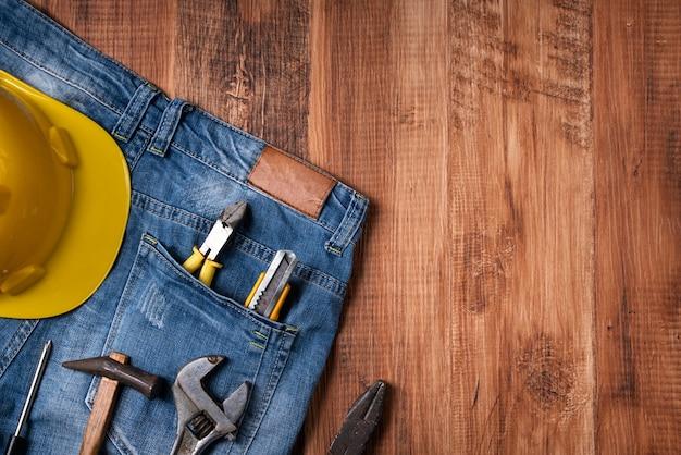 Концепция дизайна вид сверху дня труда с рабочими инструментами и джинсами на фоне деревянного стола.