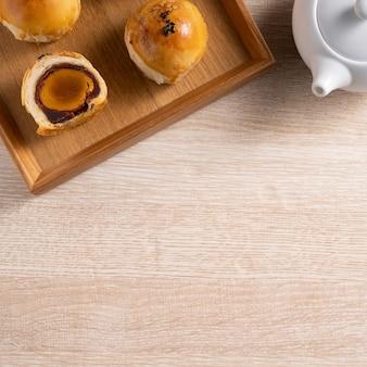 月餅ヨークペストリー、木製のテーブルの背景に中秋節の休日の月餅の平面図デザインコンセプト