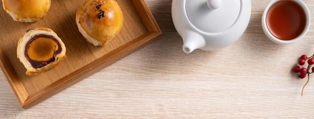 月餅卵黄ペストリー、木製のテーブルの背景に中秋節の休日の月餅の平面図デザインコンセプト