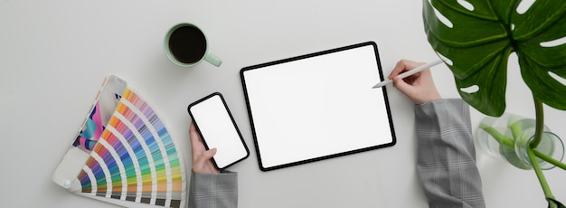 Top view of designer working on mock-up smartphone and tablet on marble table