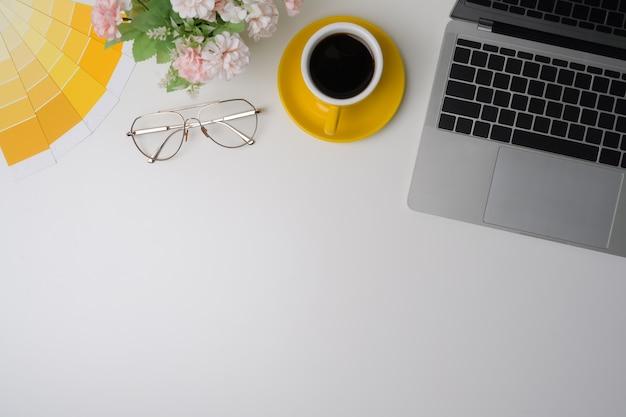 Рабочее место дизайнера вид сверху с портативным компьютером, кофейной чашкой и очками на белом столе.