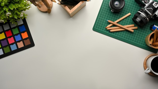 Top view of designer workspace with paint tools, camera, coffee cup and copy space, creative mock up scene