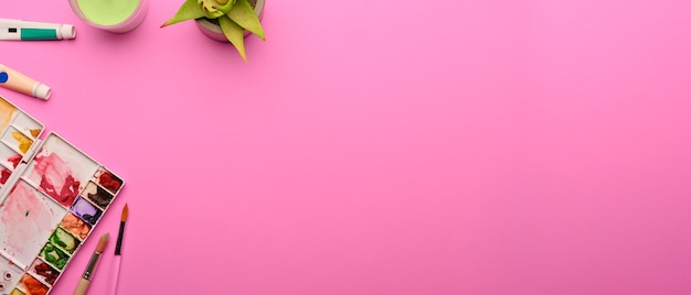 Top view of designer workspace with paint tools decorations and copy space on pink background