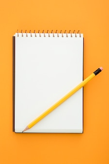 Top view desk arrangement with empty notepad on orange background