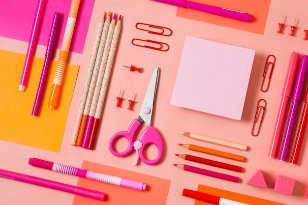 Top view desk arrangement with pink items