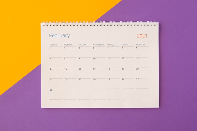 Top view desk calendar on contrasted coloured background