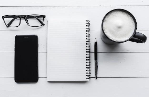 Стол офисный вид сверху с блокнотом, ручка, кофе на белом фоне