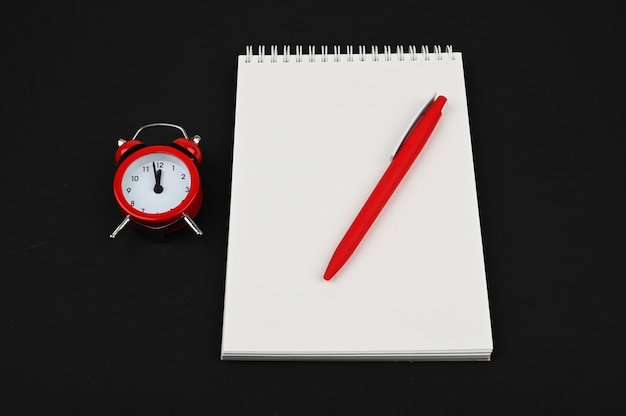 Top view desk above of open notebook with pencil and red alarm clock on black tbackground.