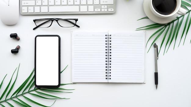 スマートフォンの空白の白い画面とオフィスで利用可能なデバイスを備えたトップビューデスクの空白。