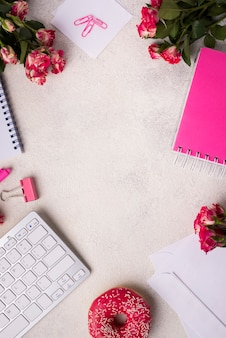 Top view of desk with keyboard and bouquet of roses