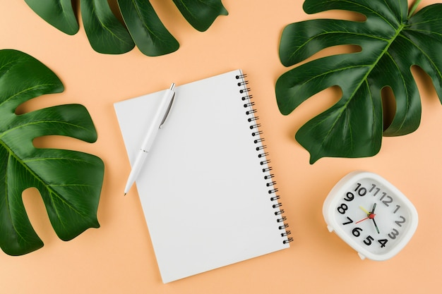 Top view of desk with notebook with leaves and clock