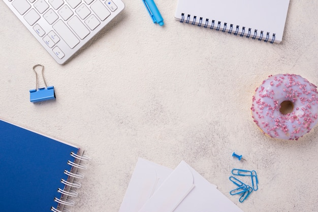Top view of desk with notebooks and doughnut