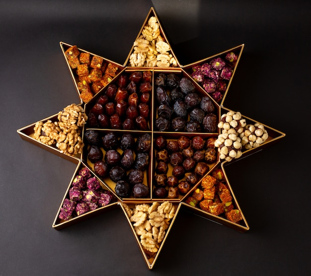 A top view desk with nuts and different dried fruits on the dark surface