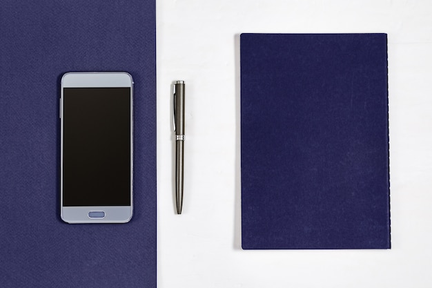Top view on desk with smartphone, notebook, pen.