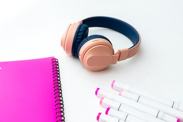 Top view of the desktop. professional multi-colored markers, pink folder, headphones