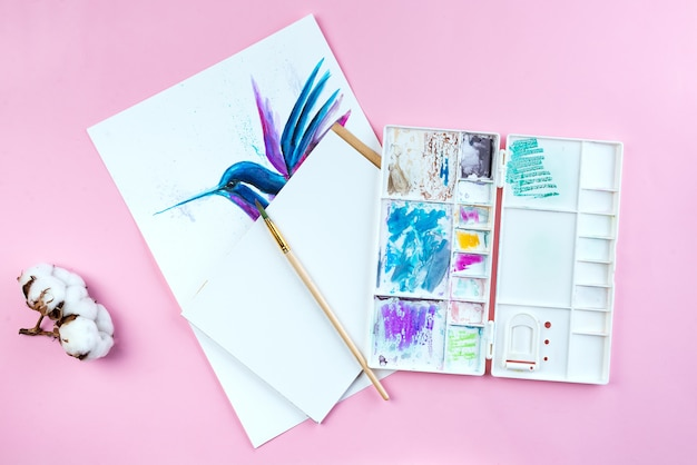 Top view of desktop workplace artist with tools - brushes, watercolor paint, notebook on pink background