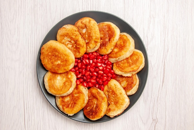 Top view dessert appetizing pancakes and seeds of pomegranate on the black plate on the white table