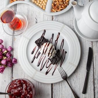 Dessert di vista superiore in piatto con tè, noci, marmellata di frutta, fiori su fondo di legno bianco.