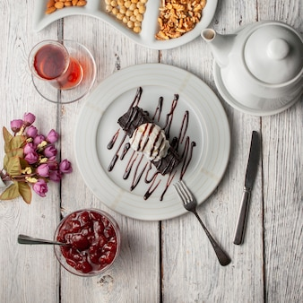 Top view dessert in plate with tea, teapot nuts, fruit jam, flowers on white wooden background.