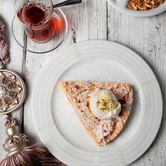 Dessert di vista superiore in piatto con tè su fondo di legno bianco. verticale