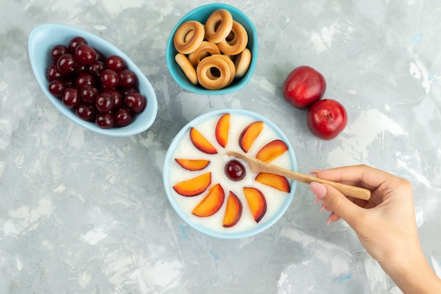 Top view dessert with fruits sliced fruits along with sweet crackers fresh fruits on white