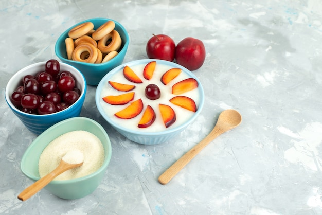 Top view dessert with fruits sliced fruits inside plate along with sweet crackers fresh fruits on white