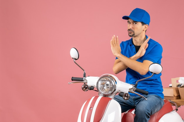 Top view of determined courier guy wearing hat sitting on scooter delivering orders making stop gesture on pastel peach background