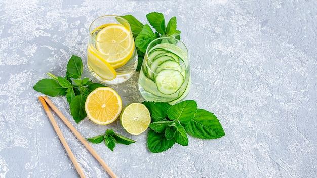 Водный напиток для детоксикации с огурцом и лимоном на светло-сером текстурированном фоне, вид сверху