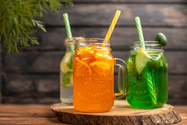 Top view of detox water and fresh juice in bottles with tubes on the left side on brown wooden background