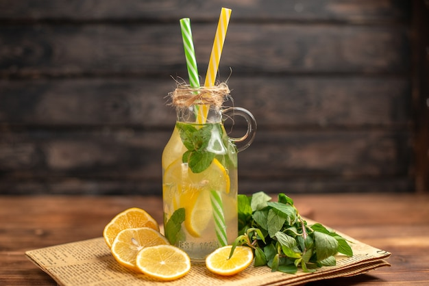 Top view of detox water made of lemon and mint on an old newspaper on brown wooden background