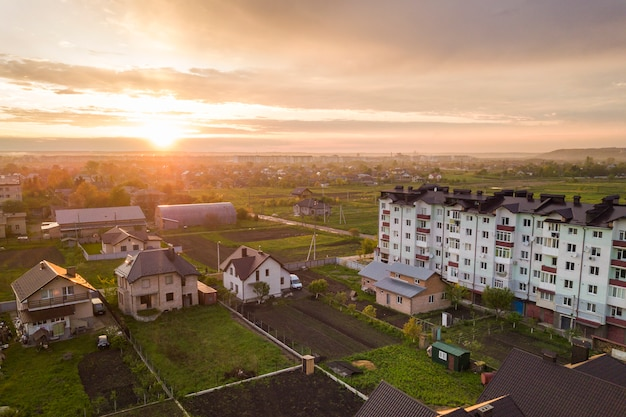 Top view of developing city landscape. apartment building and suburb house roofs on pink sky at sunrise background.