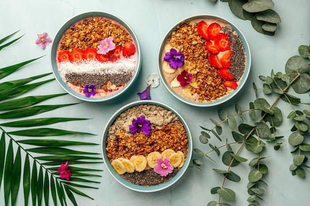 Top view on dfferent smoothie bowls with fruits and granola
