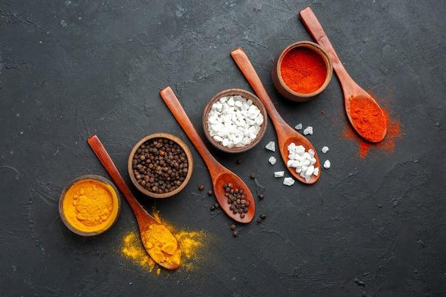 黒いテーブルの上のターメリック黒胡椒sae塩赤唐辛子粉木のスプーンと上面図斜め列ボウル