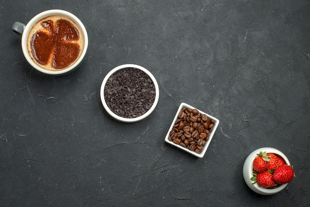 Top view diagonal row a cup of coffee bowls with strawberries chocolate coffee seeds on dark background