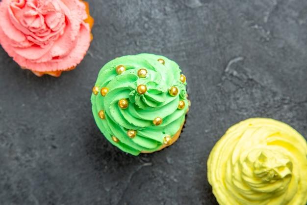 Mini cupcakes colorati in fila diagonale vista dall'alto su superficie scura