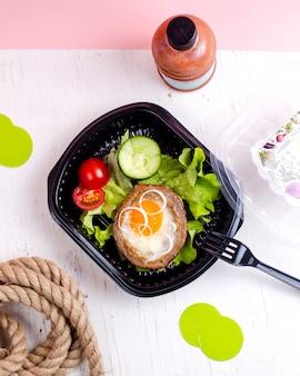 Vista dall'alto dieta colazione uovo fritto nel pane nero con una fetta di cetriolo e pomodoro con una bottiglia di disintossicazione