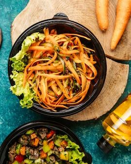 Вид сверху диетический салат из моркови и огурцов с салатом на доске