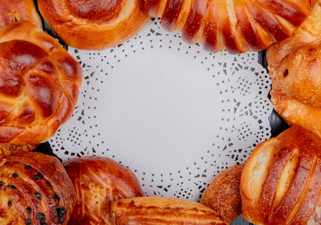 Top view of different bakery products set in round shape around doily paper as background